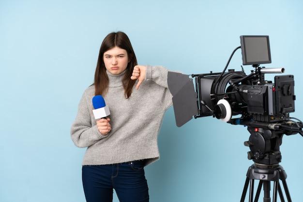 Jeune reporter femme tenant un microphone et rapportant des nouvelles montrant le signe du pouce vers le bas