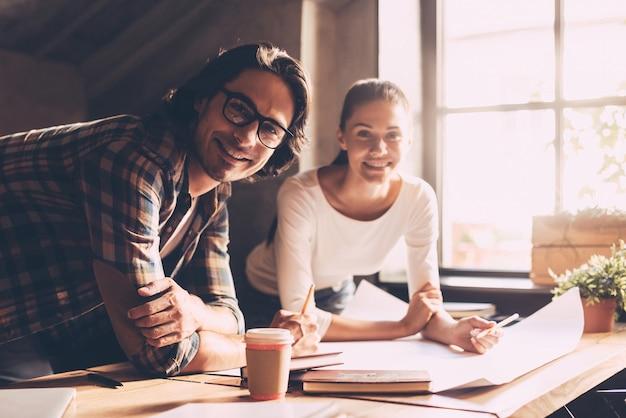 Jeune et réussi. gai jeune homme et femme regardant la caméra et souriant tout en se penchant au bureau avec un plan posé dessus