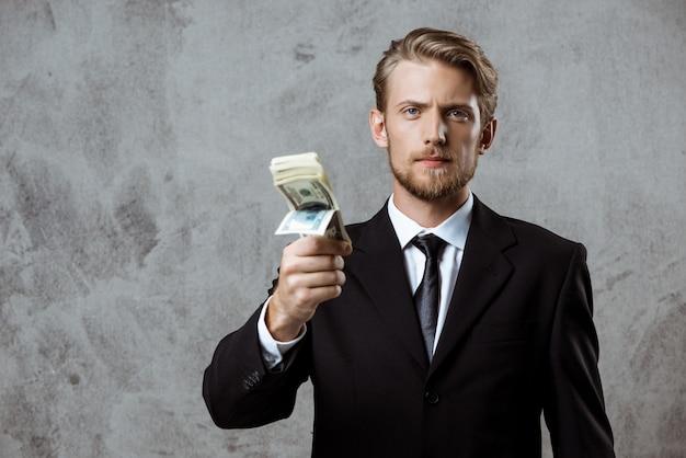 Jeune, réussi, homme affaires, complet, tenue, argent