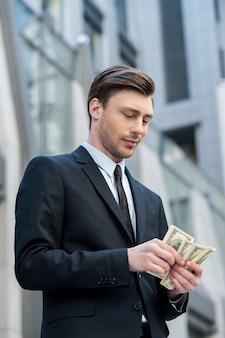 Jeune et riche. jeune homme confiant en chemise et cravate comptant de l'argent et debout à l'extérieur
