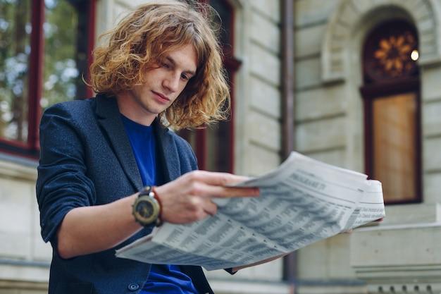 Jeune, rougeâtre, lecture journal, près, vieux, style, bâtiment