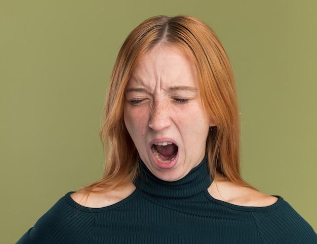 Jeune rousse agacée au gingembre avec des taches de rousseur debout avec les yeux fermés isolée sur un mur vert olive avec espace pour copie