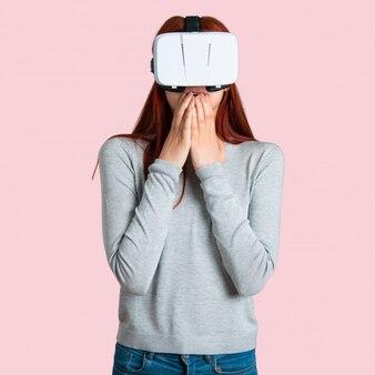 Jeune rousse à l'aide de lunettes vr. expérience de réalité virtuelle sur fond rose isolé