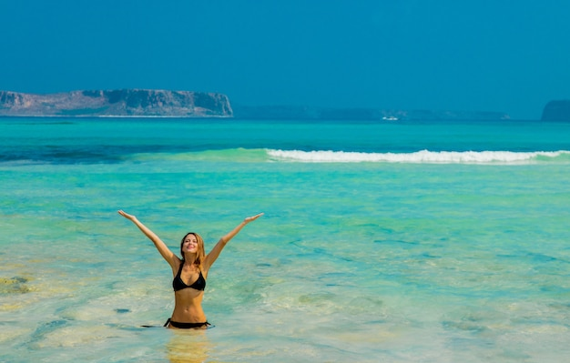 Jeune rousse en bikini noir sur la plage de balos