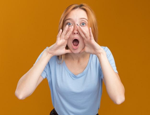 Jeune rousse choquée au gingembre avec des taches de rousseur tenant la main près de la bouche isolée sur un mur orange avec espace de copie