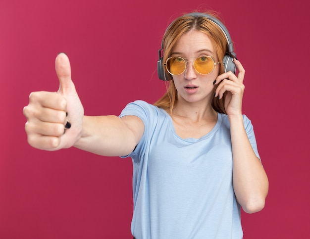 Jeune rousse confiante au gingembre avec des taches de rousseur dans des lunettes de soleil et sur des écouteurs levant le pouce