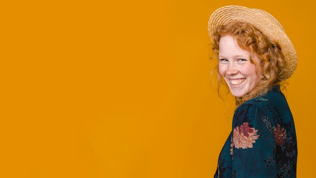 Jeune rousse à demi tournée femme à pleines dents souriant