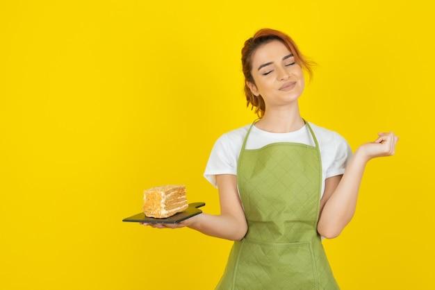Jeune rousse joyeuse avec une tranche de gâteau frais sur un mur jaune
