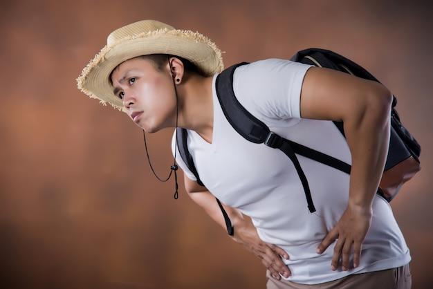 Jeune routard asiatique avec sac et chapeau