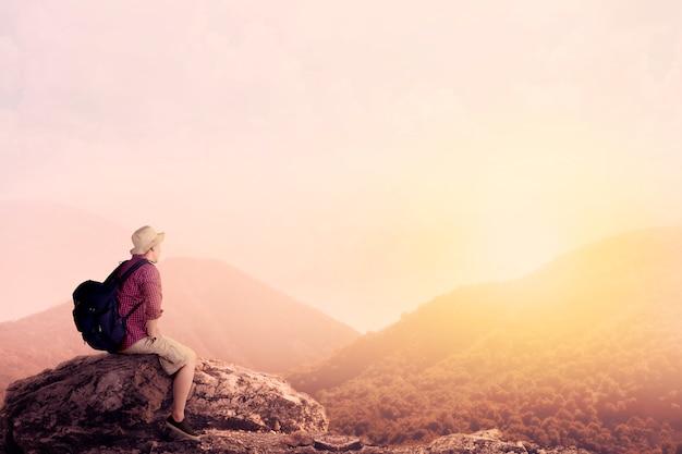 Jeune routard bénéficiant d'une vue sur la vallée