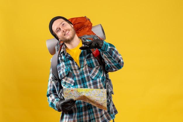Jeune routard satisfait avec des gants en cuir tenant une carte