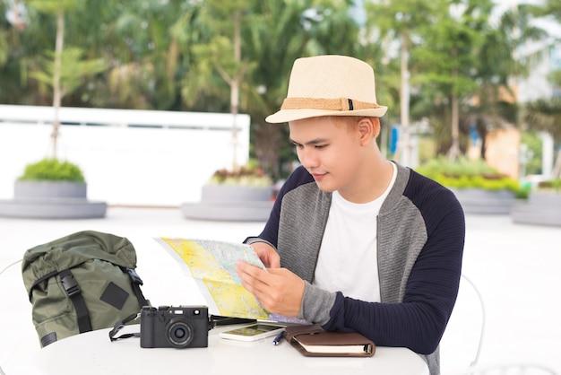 Jeune routard de voyage asiatique vérifiant la carte s'amusant dans la ville