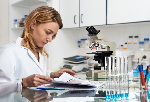 Une jeune scientifique européenne vérifie son journal de laboratoire
