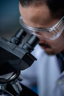 Jeune scientifique regardant à travers un microscope dans un laboratoire. jeune scientifique faisant des recherches.