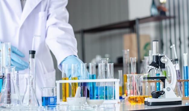 Jeune scientifique regardant à travers un microscope dans un laboratoire.