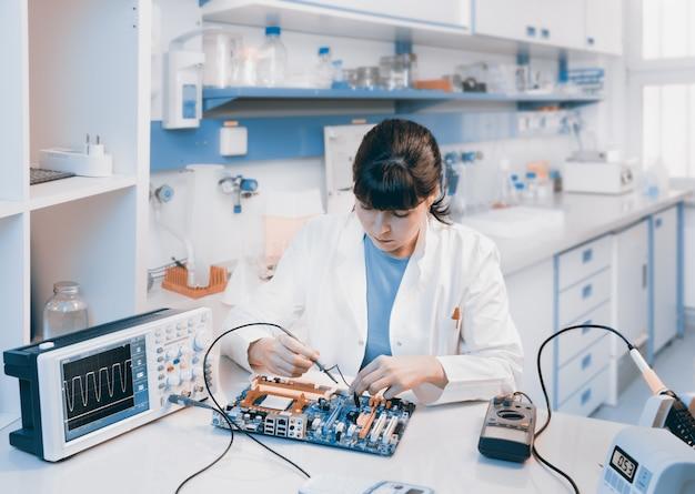 Un jeune scientifique répare un appareil électronique