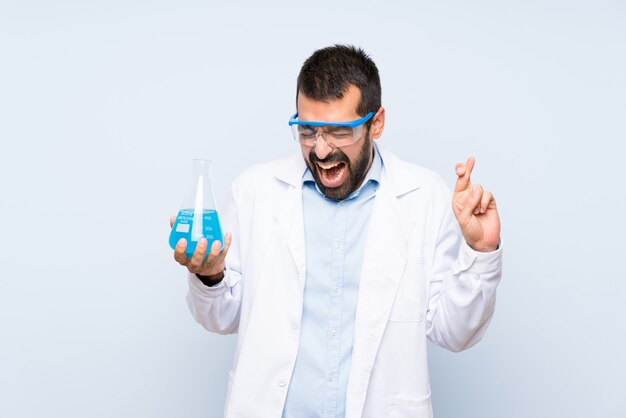 Jeune scientifique tenant la fiole de laboratoire avec les doigts croisés