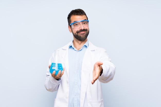 Jeune scientifique tenant la fiole de laboratoire sur fond isolé se serrant la main pour conclure