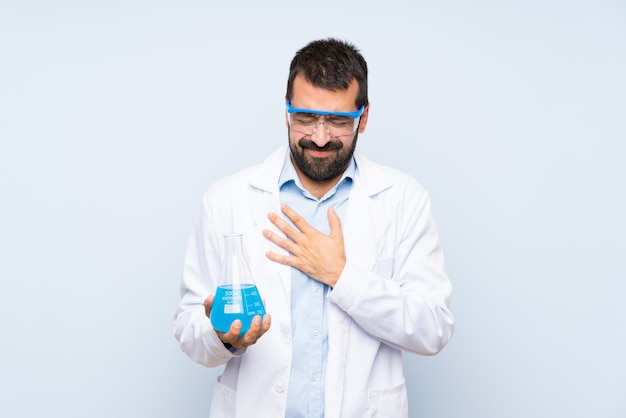 Jeune scientifique tenant flacon de laboratoire ayant une douleur dans le coeur