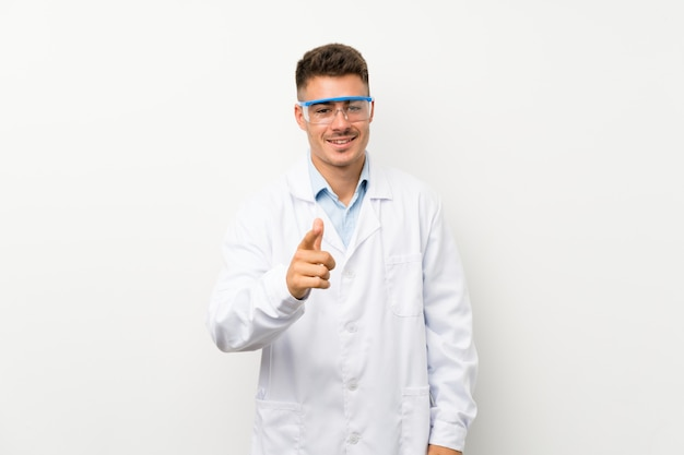 Jeune scientifique tenant flacon de laboratoire sur le mur isolé pointe le doigt vers vous