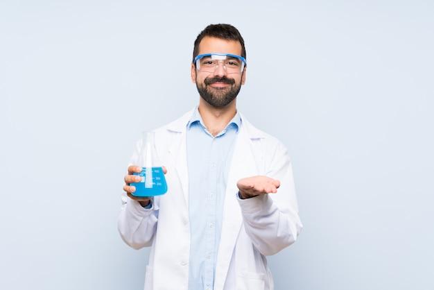 Jeune scientifique tenant un flacon de laboratoire sur un mur isolé tenant une surface imaginaire sur la paume pour insérer une annonce