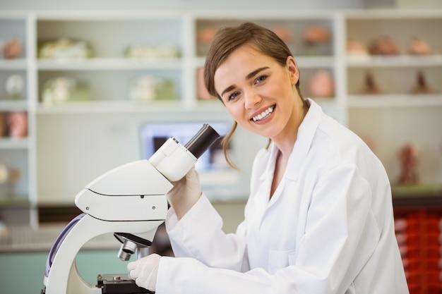 Jeune scientifique travaillant au microscope