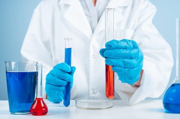 Jeune scientifique avec tube à essai faisant des recherches en laboratoire clinique. spécialiste scientifique professionnel au travail.
