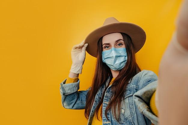 Jeune séduisante voyageuse en chapeau et gants fait selfie sur fond jaune, vêtue d'une veste en jean, porte un masque médical de protection pour se protéger du coronavirus. concept de pandémie