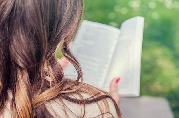 Jeune sérieux, belle fille tenant un livre ouvert, lisez le parc vert d'été. vue latérale portrait d'une jeune fille attirante jouissant d'un bon livre assis à la soirée ensoleillée en plein air