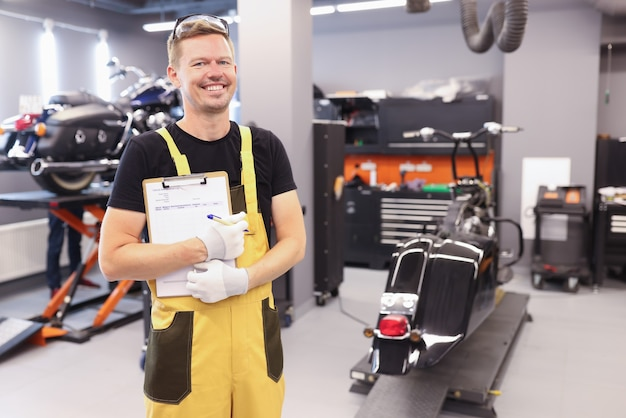 Un jeune serrurier en uniforme se tient en atelier et tient un presse-papiers avec des documents en mains
