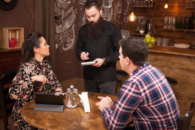 Jeune serveur barbu prenant la commande d'un jeune couple au restaurant. pub vintage.