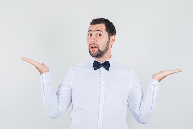 Jeune serveur en chemise blanche montrant différents types de repas et de boissons et à la joyeuse, vue de face.
