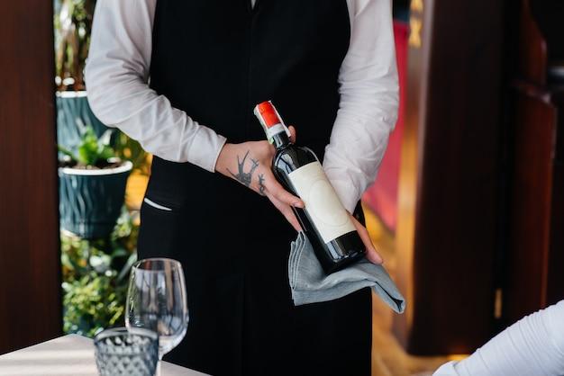 Un jeune serveur dans un tablier élégant démontre et offre un bon vin à un client dans un restaurant. service clients.