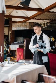 Un jeune serveur masculin dans un uniforme élégant est occupé à servir la table dans un beau restaurant gastronomique. activité de restauration, du plus haut niveau.