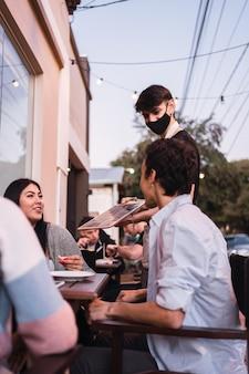 Un jeune serveur portant un masque dans un bar recommande le menu du jour.