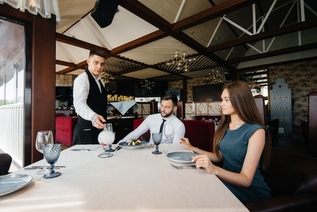 Un jeune serveur en tablier élégant sert une table avec un beau couple dans un restaurant raffiné. service clients.