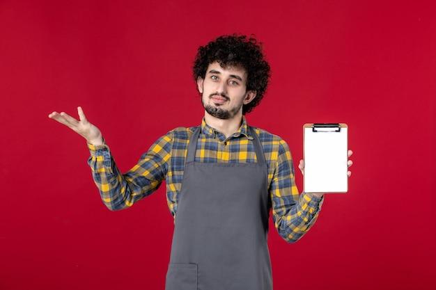 Jeune serveur de type curieux aux cheveux bouclés tenant un carnet de chèques sur fond rouge isolé