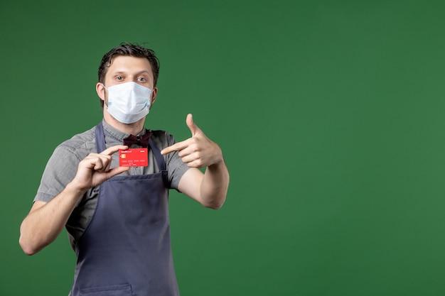 Jeune serveur en uniforme avec masque médical et montrant une carte bancaire faisant un geste correct sur fond vert