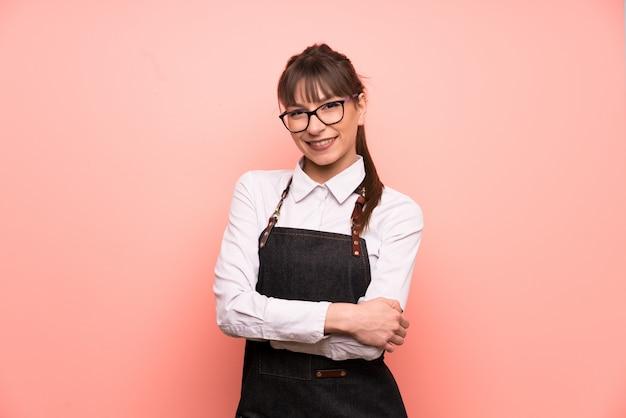 Jeune serveuse sur fond rose en riant