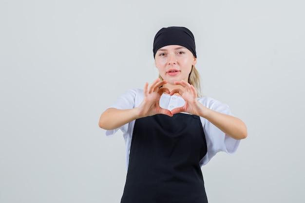 Jeune serveuse montrant le geste du cœur en uniforme et tablier