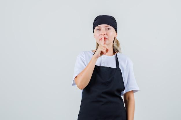 Jeune serveuse montrant le geste de silence en uniforme et tablier et à la prudence