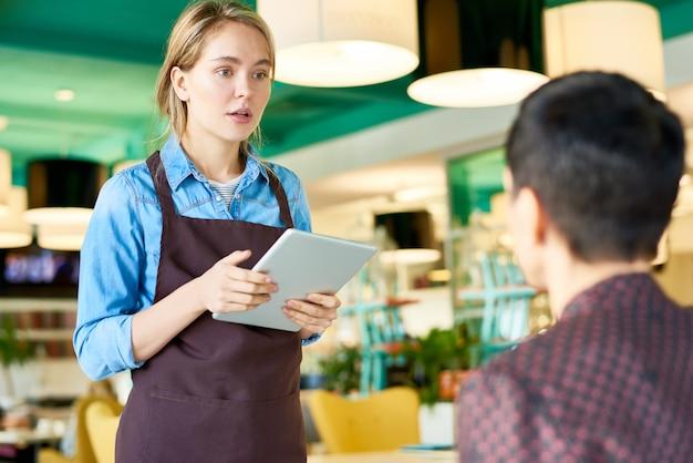 Jeune, serveuse, prendre commandes, dans, café