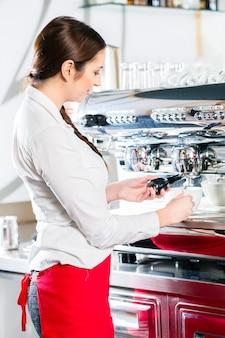 Jeune serveuse de race blanche à l'aide d'une machine à café automatique