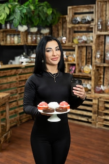 Une jeune serveuse sert un café client dans une tasse en carton jetable et un dessert