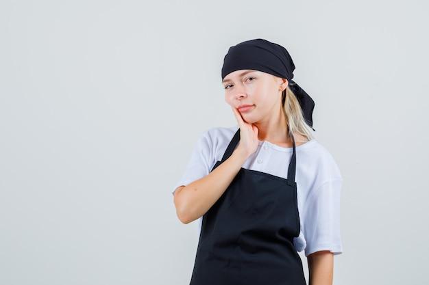 Jeune serveuse souffrant de maux de dents en uniforme et tablier