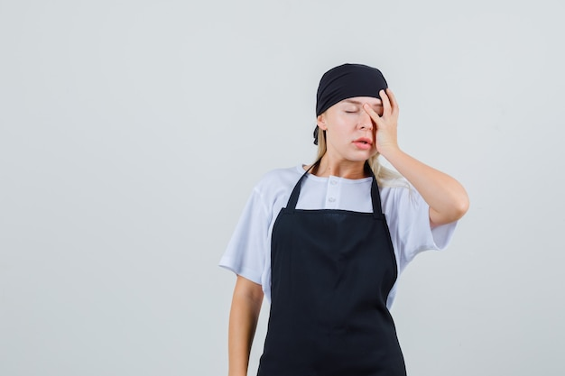 Jeune serveuse tenant la main sur le visage en uniforme et tablier et à oublier
