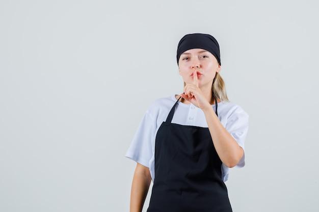 Jeune serveuse en uniforme et tablier montrant le geste de silence et à la prudence