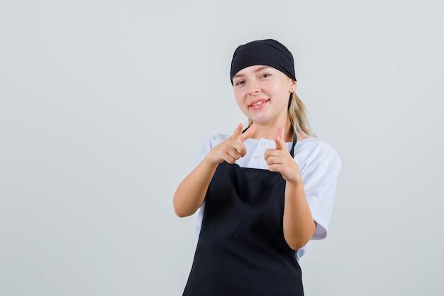 Jeune serveuse en uniforme et tablier pointant et à la joyeuse