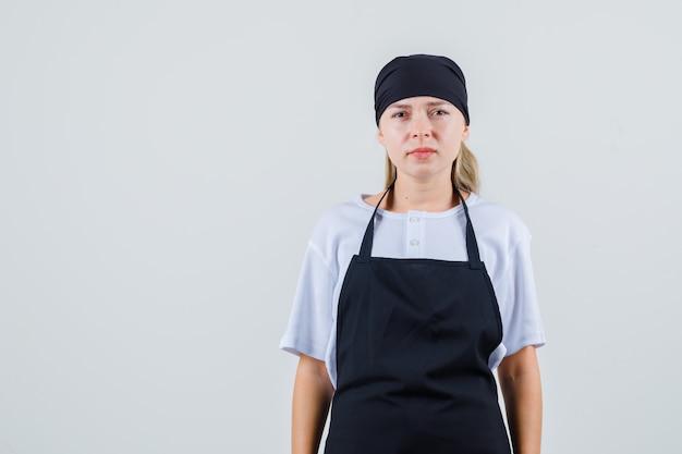 Jeune serveuse en uniforme et tablier à la recherche et à la déception