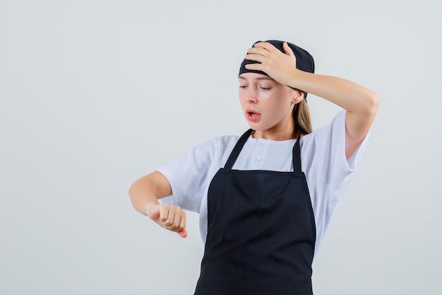 Jeune serveuse en uniforme et tablier regardant son bras et à la confusion
